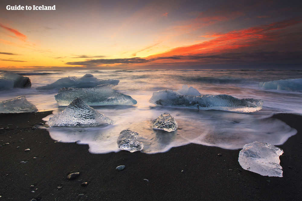 冰岛南岸钻石冰沙滩上的冰块在午夜阳光下熠熠生辉