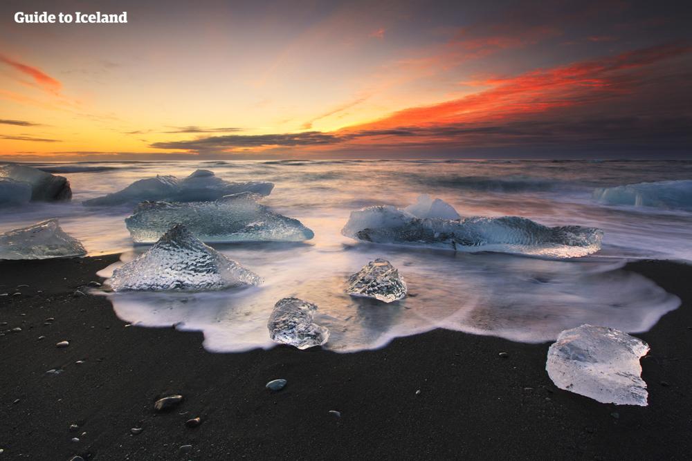 백야의 태양에 다이아몬드 해변을 장식한 얼음조각이 빛의 공연장으로 변신합니다.