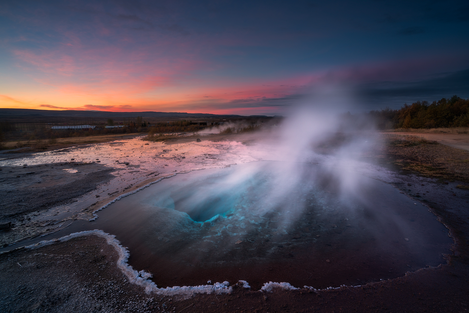 Strokkur hot spring erupting, gushing boiling geothermal water high into the air.