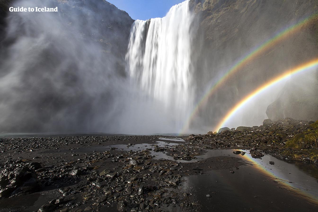 Der Wasserfall Skogafoss lässt beim Auftreffen auf den darunterliegenden schwarzen Steinen einen Regenbogen entstehen.