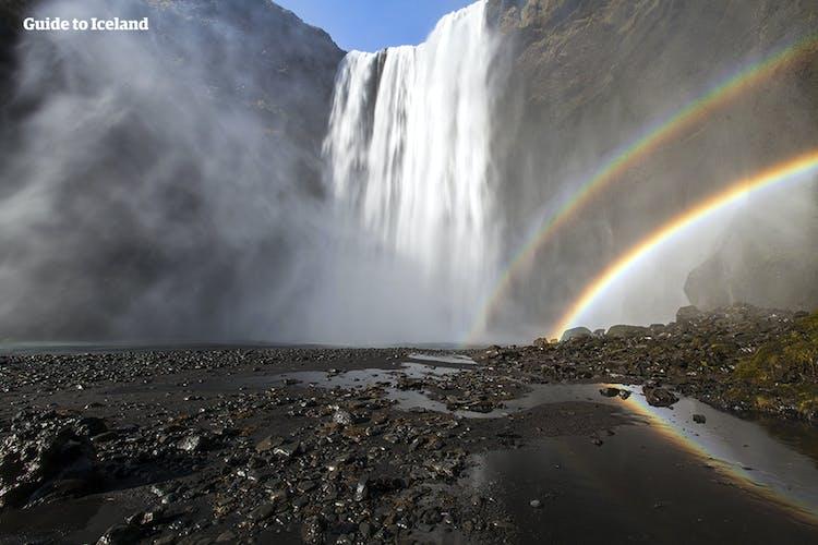 Wodospad Skógafoss tworzy tęczę, która ląduje na czarnych skałach poniżej.