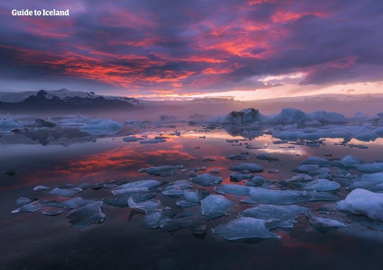 La laguna glaciar Jökulsárlón al atardecer, con el hielo que refleja suavemente los últimos rayos dorados y rosados del sol de verano.