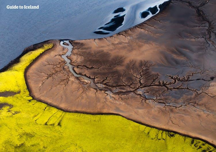 Ein Wanderer in Landmannalaugar ruht sich auf einem der schönen Aussichtspunkte im isländischen Hochland aus und genießt das Panorama mit seinen Bergen, Flüssen und moosbedeckten Lavafeldern.