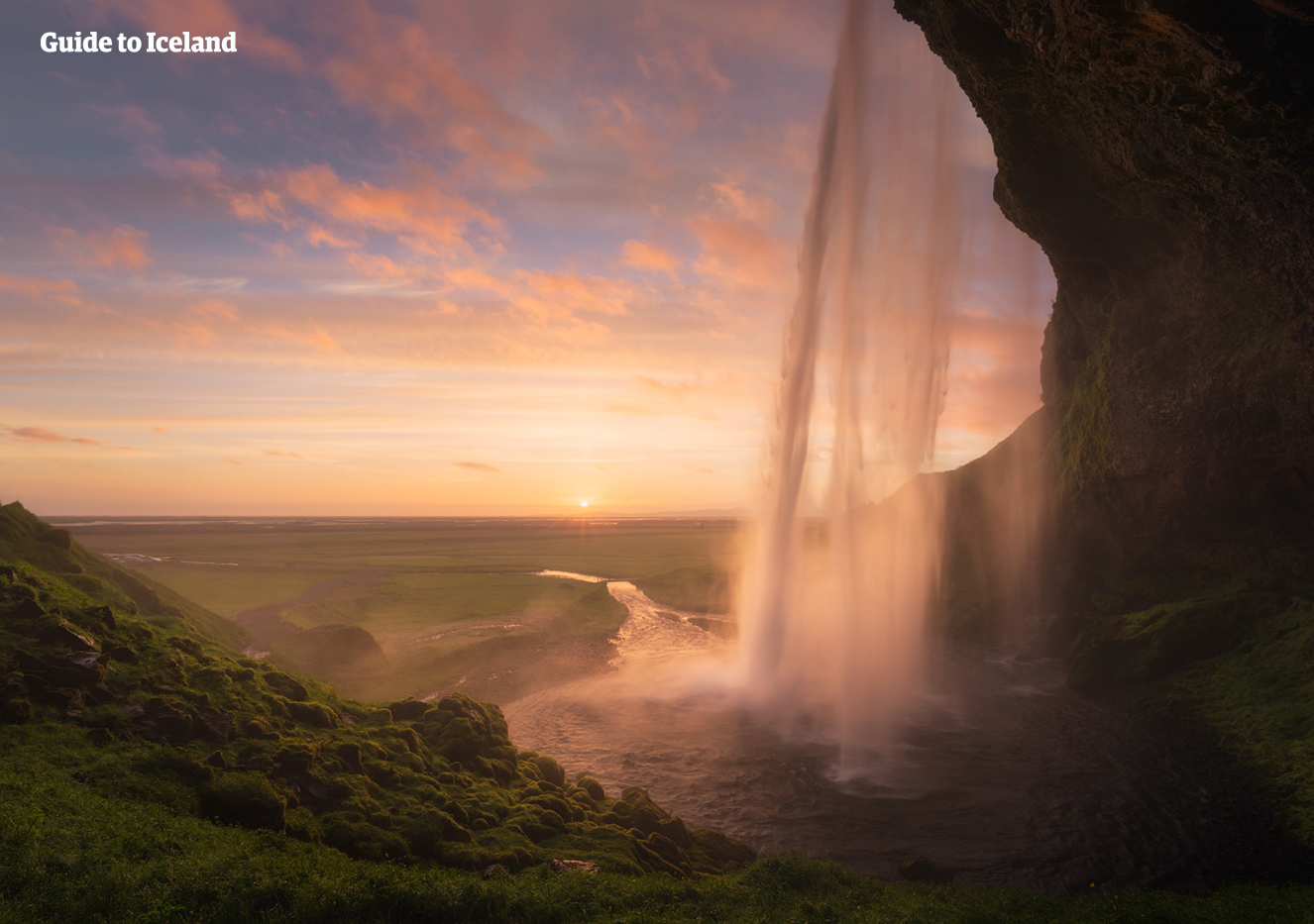 Seljalandsfoss Waterfall painted gold by the midnight sun of summer in South Iceland.