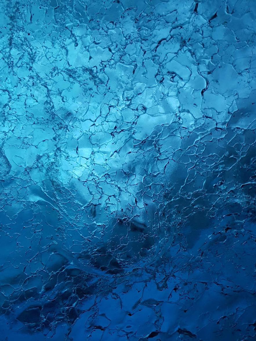 Feine Musterung in der Eiswand der Gletscherhöhle auf Island.