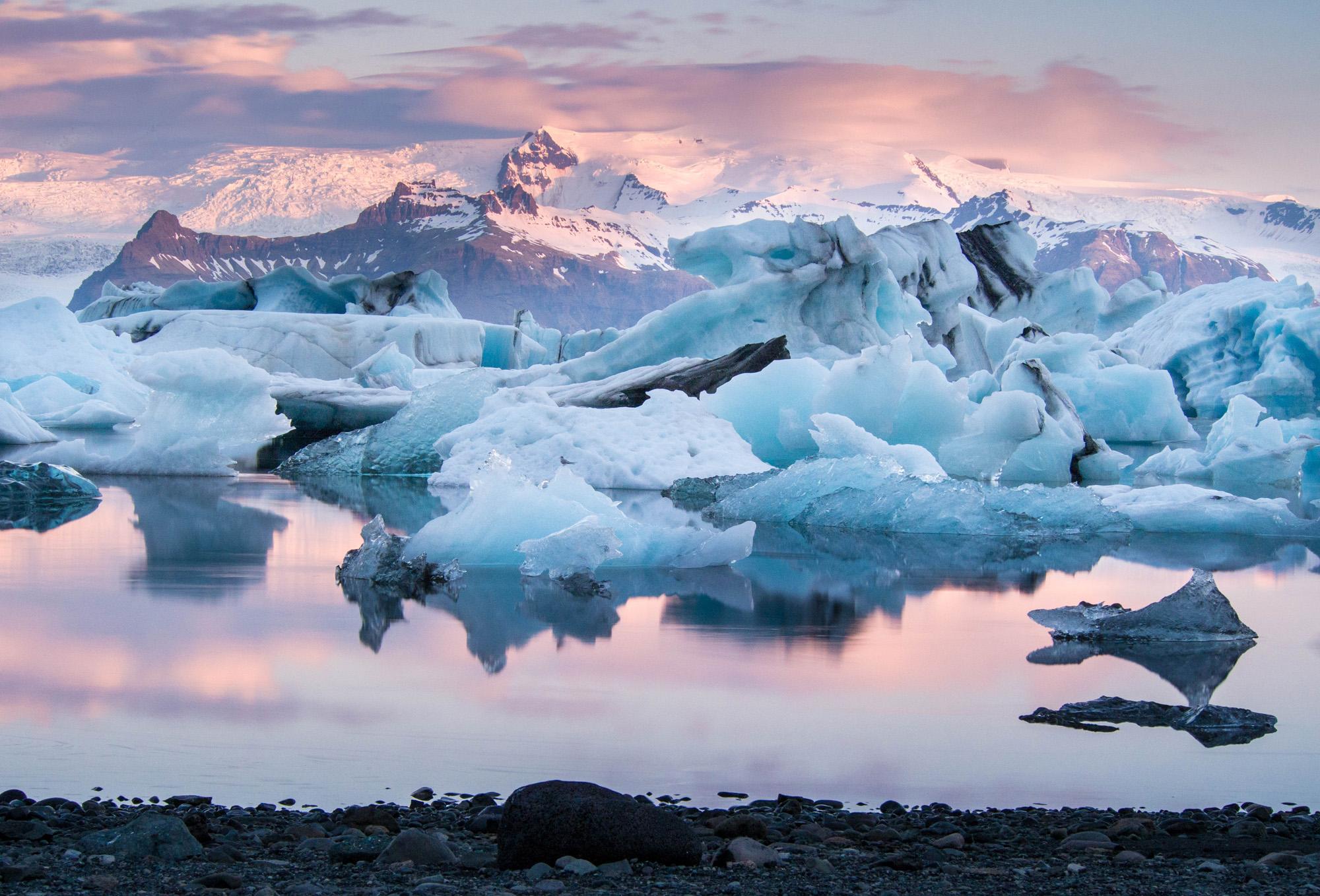 The Jökulsárlón Glacier lagoon under a pink hued sky.