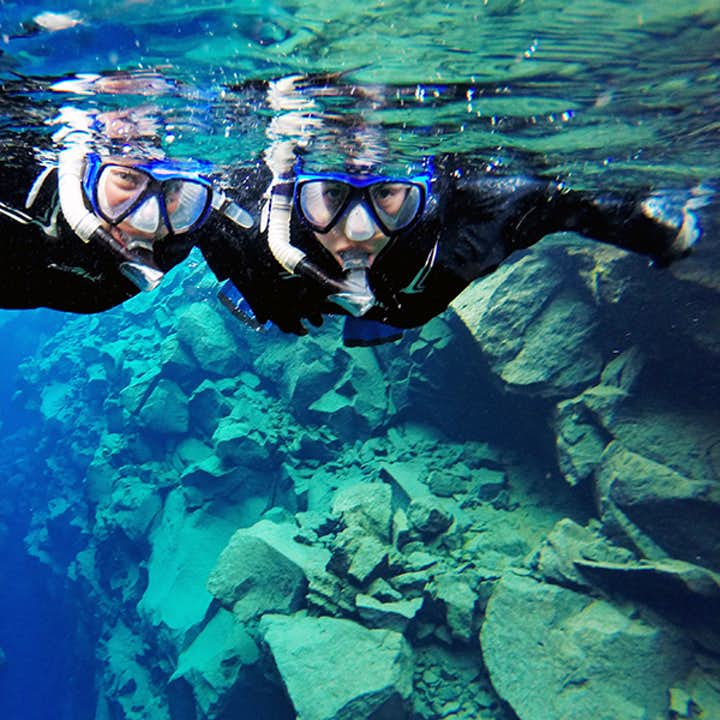 Two cheerful people on a Silfra fissure snorkeling tour