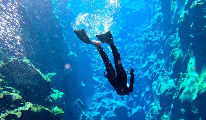 A tour participant uses flippers to dive down further into Silfra