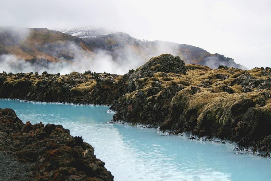 Der Kontrast der Farben des Wassers der Blauen Lagune und der moosbedeckten Lave auf Island - Guide to Iceland