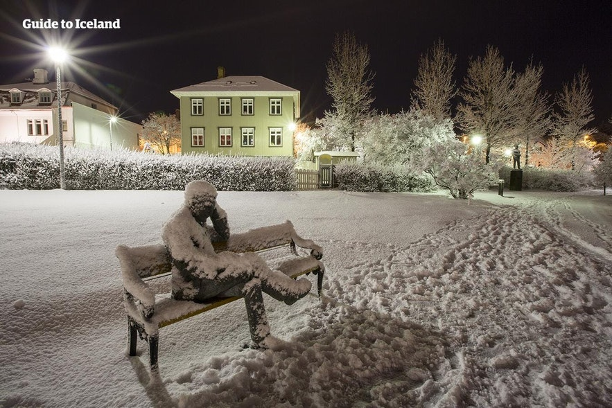 A snow covered statue by the pond in Reykjavik