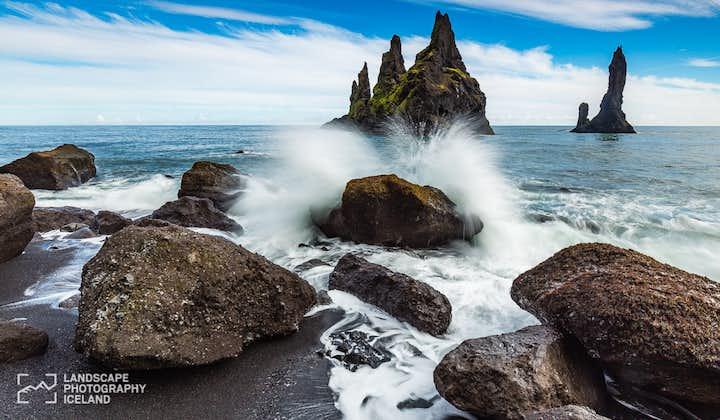 A wave breaks on the shore near Reynisdrangar sea stacks
