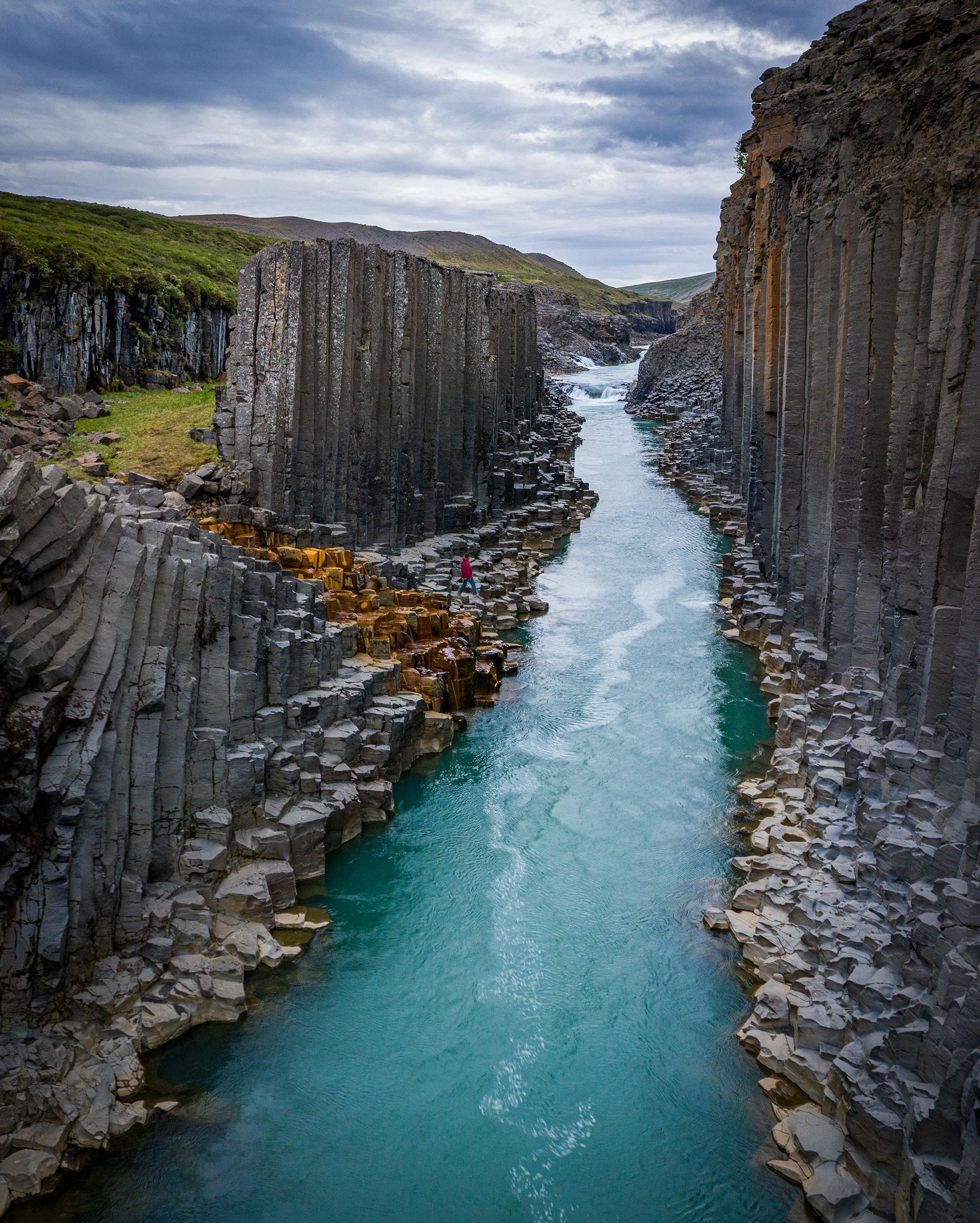 Hexagonal basalt rock column walls lining a river canyon in east Iceland.