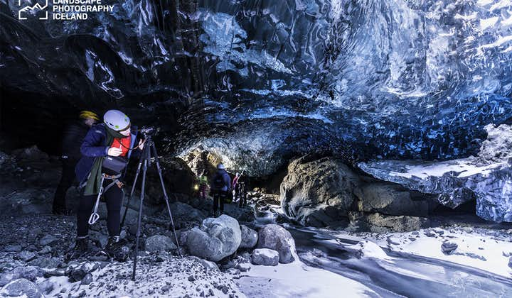 A traveller taking pictures from the inside of an ice cave.