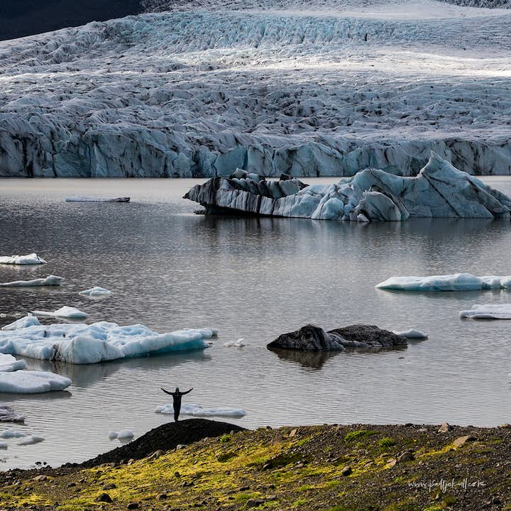 A person standing at the edge of Jokulsarlon Glacier Lagoon photographed in summer.