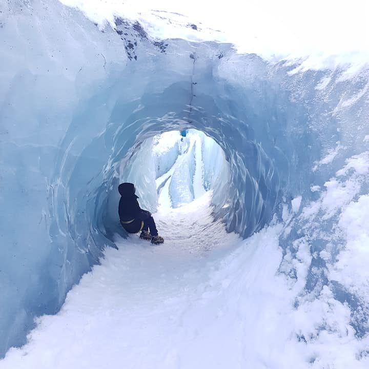 Woman sitting in an ice tunnel at Sólheimajökull Glacier