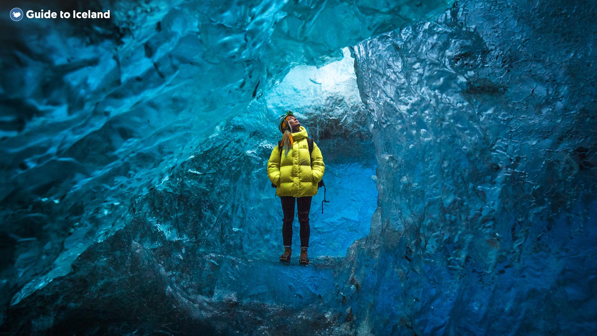 Kvinna i gul kappa vid Vatnajökulls isgrotta
