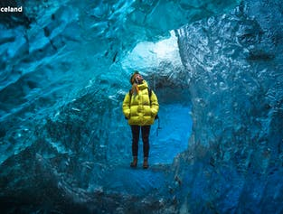 Una donna con una giacca gialla nella grotta di ghiaccio di Vatnajokull