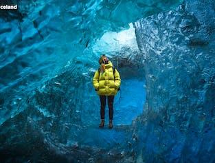 Женщина в желтой куртке на фоне ледниковой пещеры