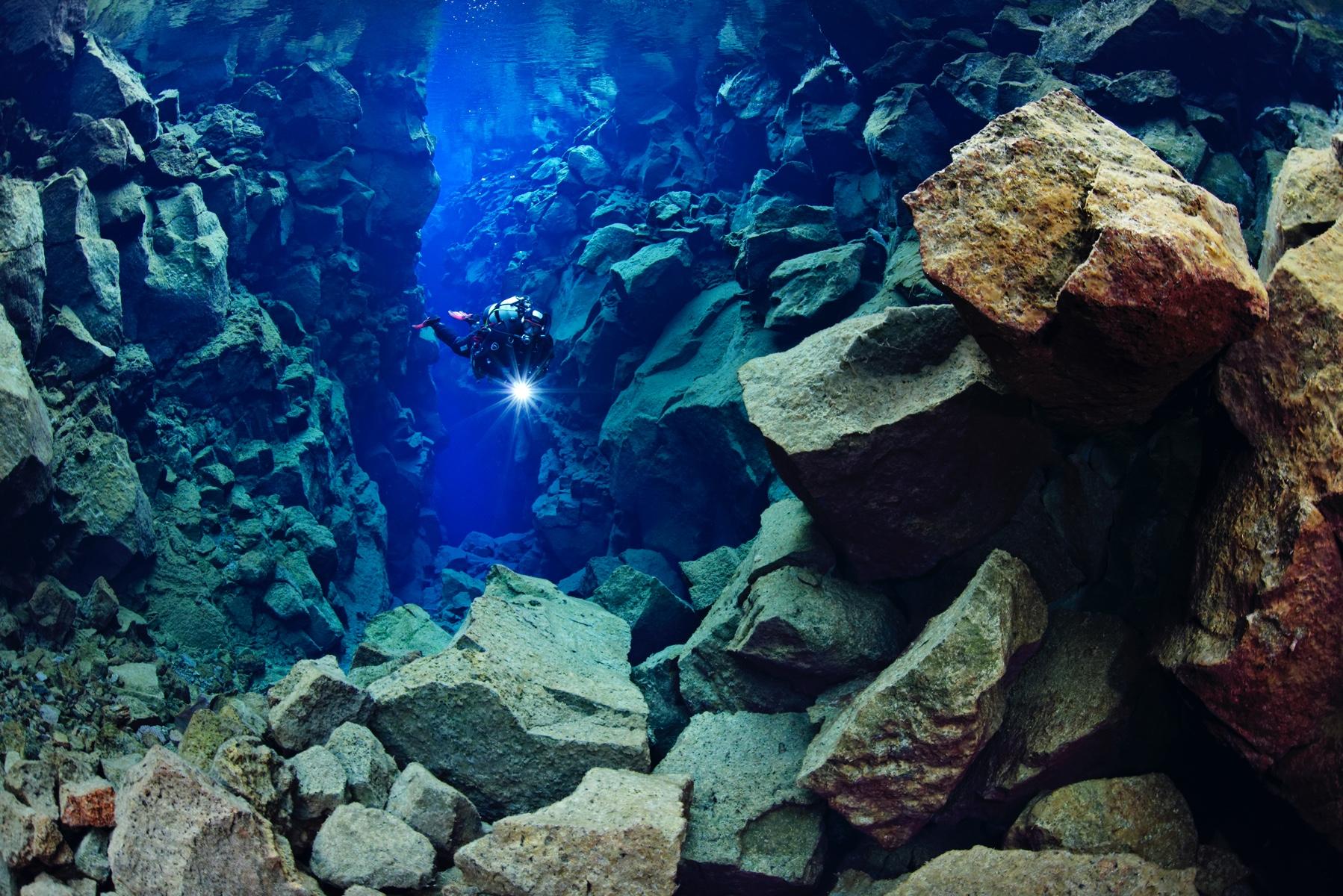 Un uomo che nuota a Silfra con una luce