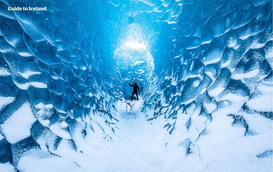 A man wields an ice axe in a blue ice cave
