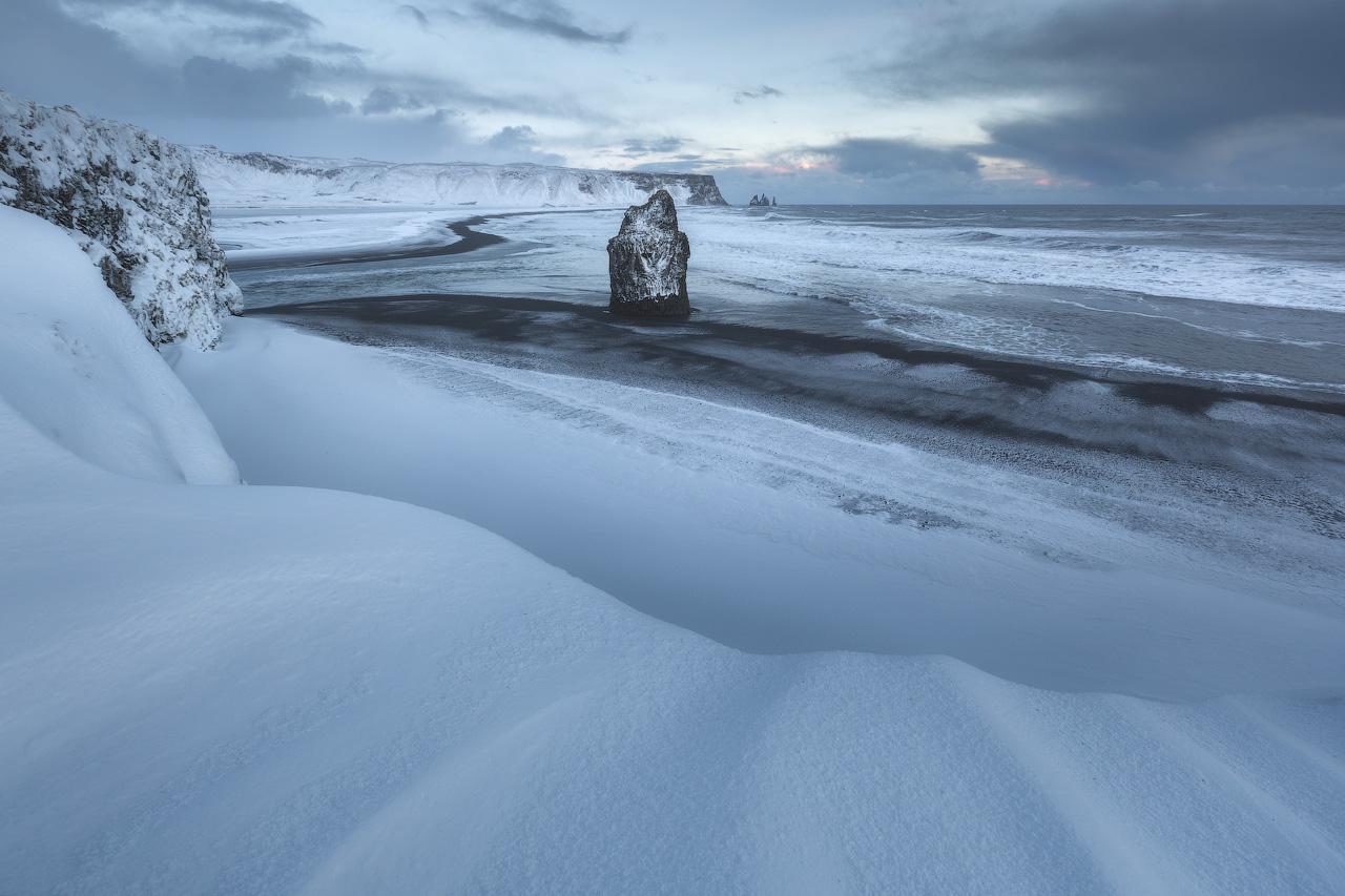 Der schwarze Sandstrand Reynisfjara unter eine Schneedecke im Winter