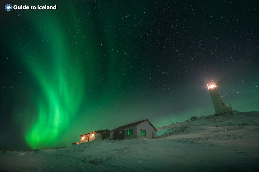 The Northern Lights shine bright behind scene with a house and lighthouse