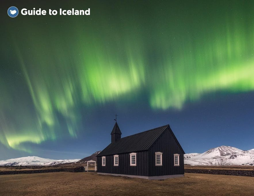 The Northern Lights light up the sky above the black church at Budir