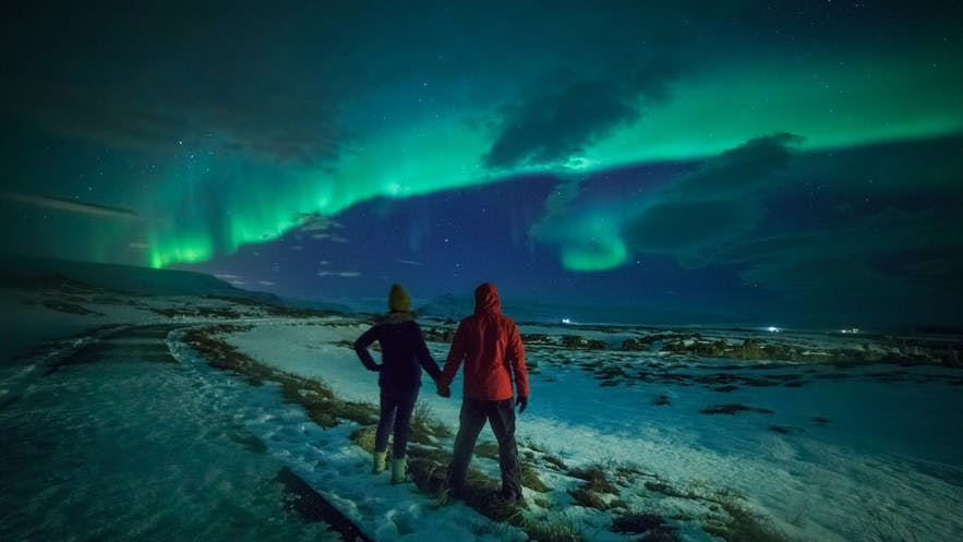 Two people hold hands under the Northern Lights in Iceland