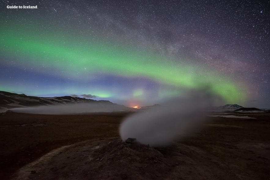 The Northern Lights shine brightly over a geothermal area in Iceland