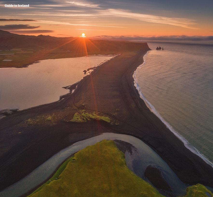 Luftfoto af den sorte sandstrand Reynisfjara i den gyldne time