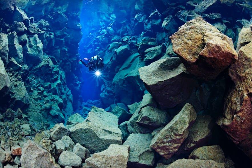 Mand dykker i Silfra-spalten med en lygte i hånden