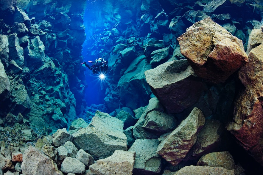 Mann dykker i Silfra-kløften med en lykt i hånden
