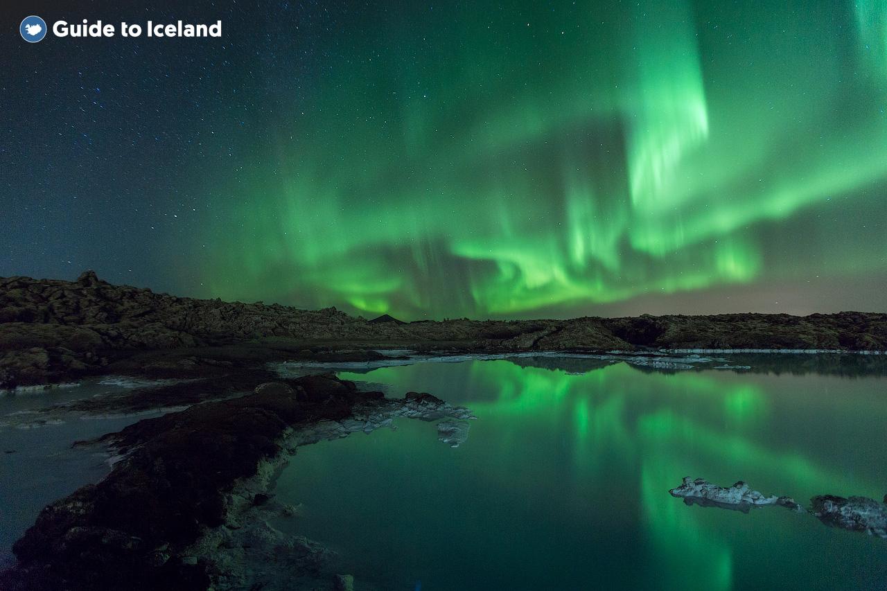 Aurores boréales au-dessus d'un des lacs de la péninsule de Reykjanes en Islande.