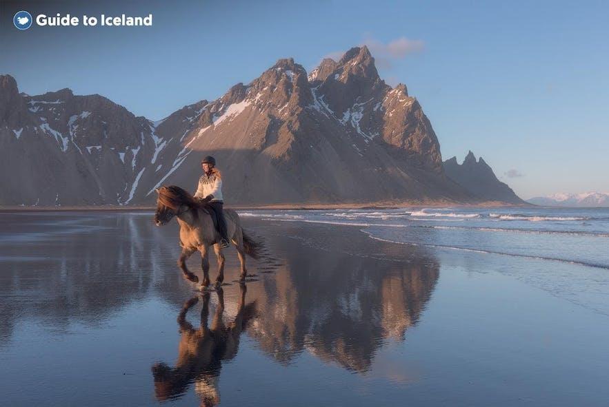 Eine Frau reitet auf einem Pferd auf der Halbinsel Stokksnes.