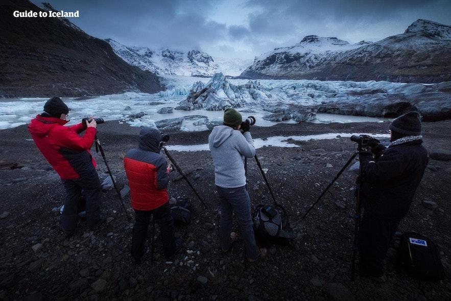 Eine Reisegruppe stellt Stative auf, um einen Gletscher zu fotografieren.