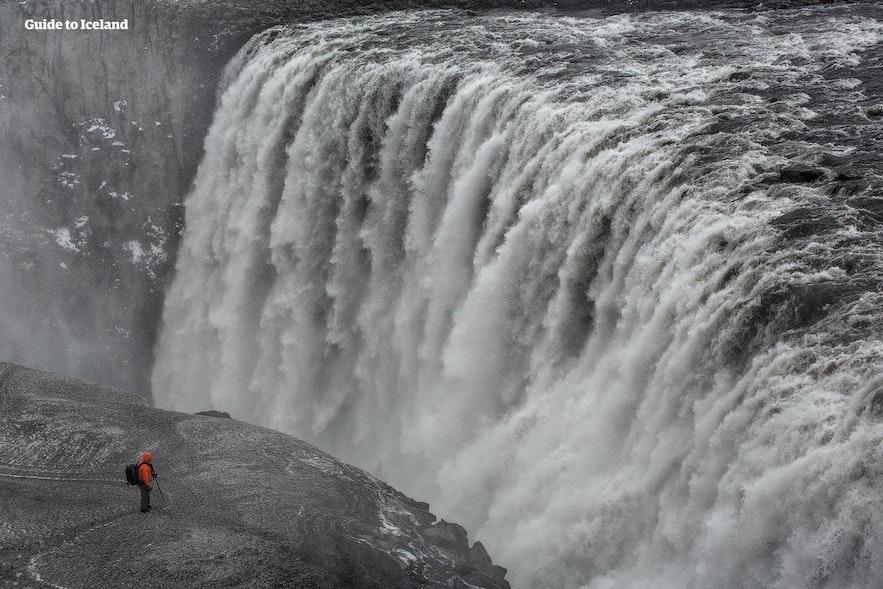 Ein Mann, der auf einer Klippe steht, sieht im Vergleich zum nahe gelegenen Dettifoss-Wasserfall winzig aus.