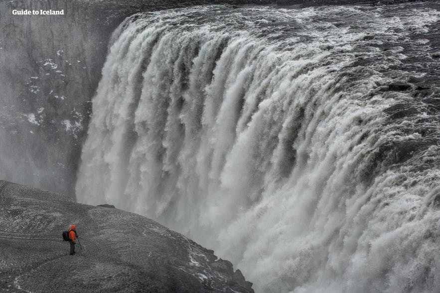 A man standing on a cliff looks minuscule compared to the nearby Dettifoss waterfall