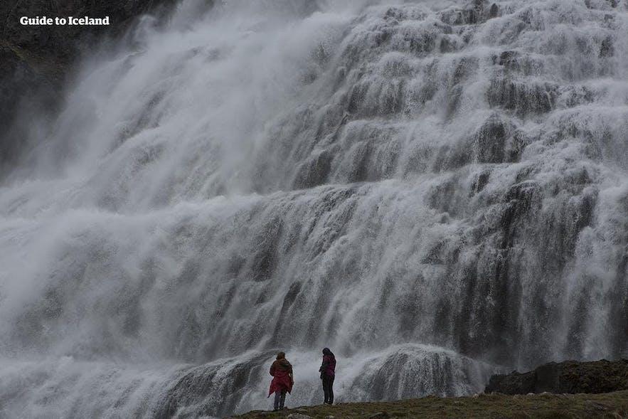 Zwei Personen am Fuße des Dynjandi-Wasserfalls