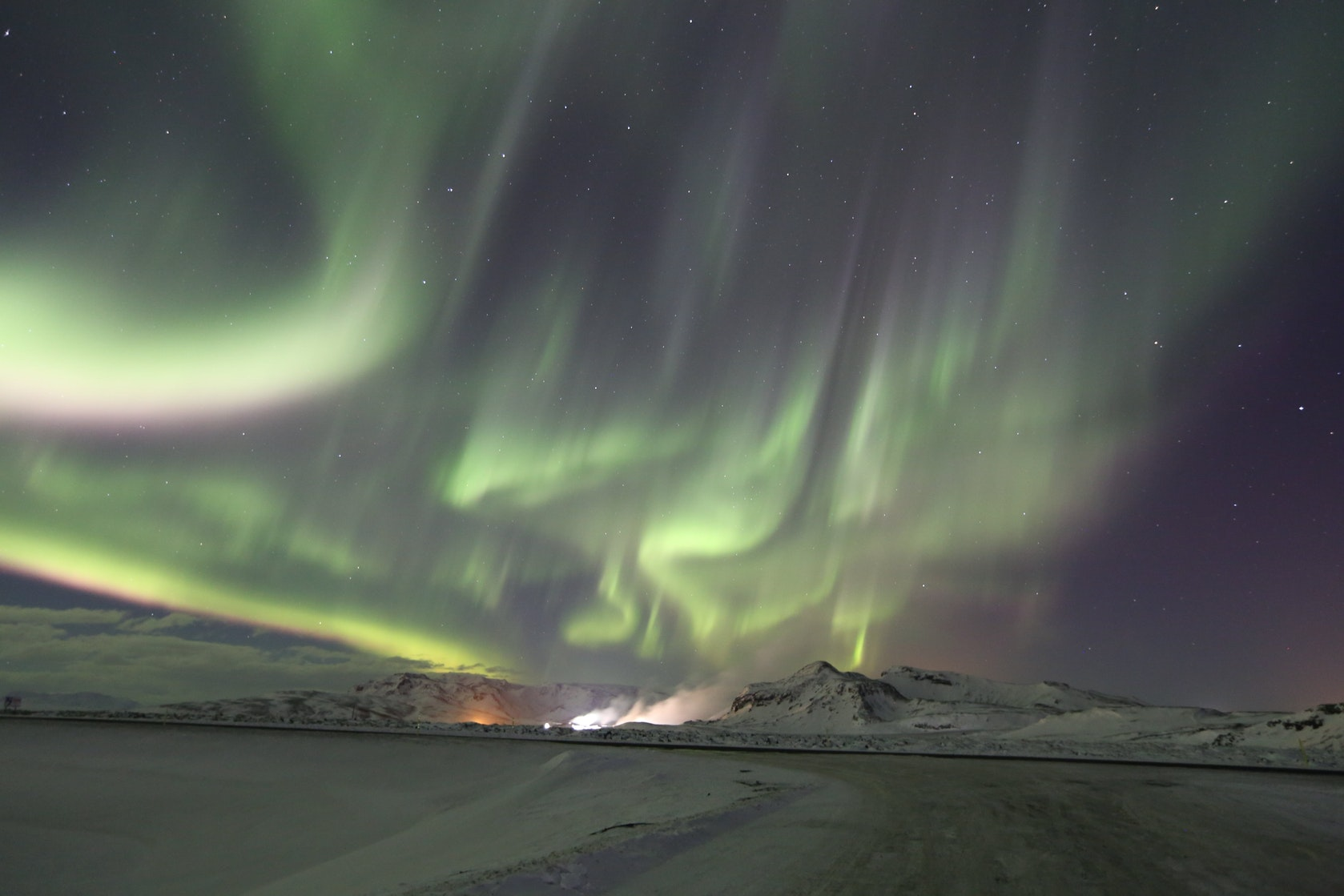 The Northern Lights dancing over a snowy mountain