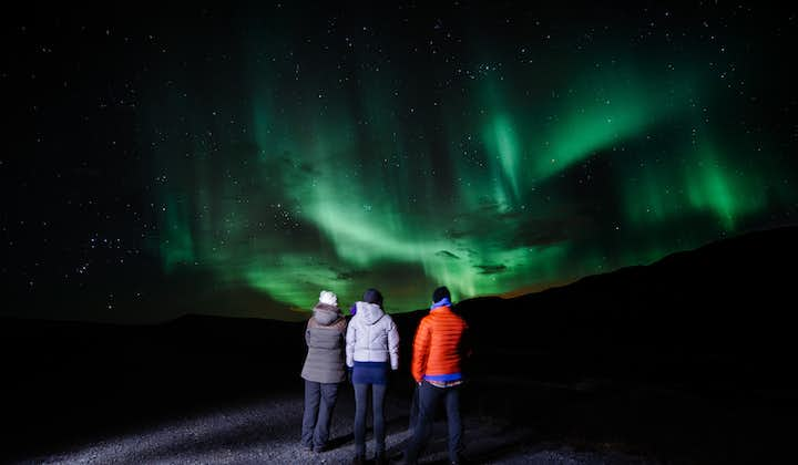 A group of three people standing looking up at the Northern Lights in Iceland