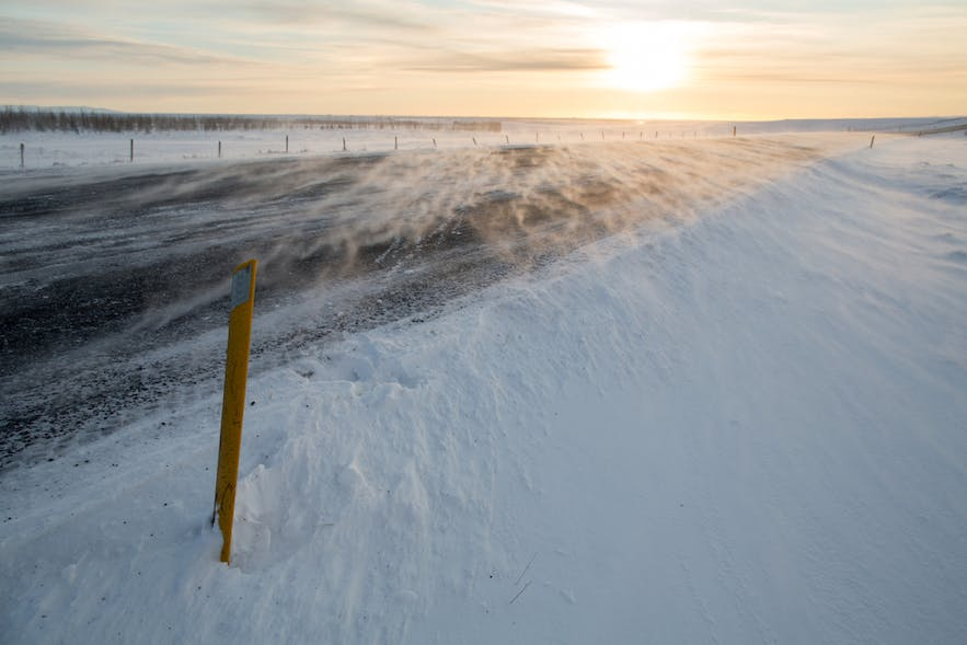 Snow blowing over a road in rural Iceland under high wind conditions