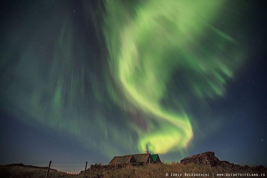 아이슬란드 교외 지역의 잔디 주택 너머로 빛나는 오로라