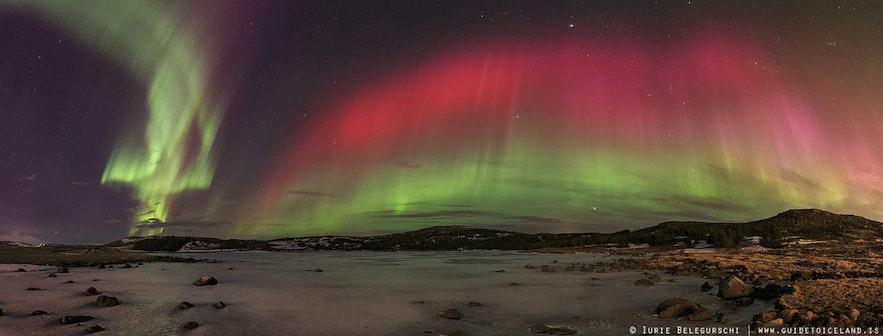 눈 덮인 아이슬란드 풍경 위로 너울거리는 핑크색이 뚜렷한 오로라의 모습