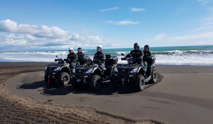 A group of people on ATVs on one of Iceland's black sand beaches