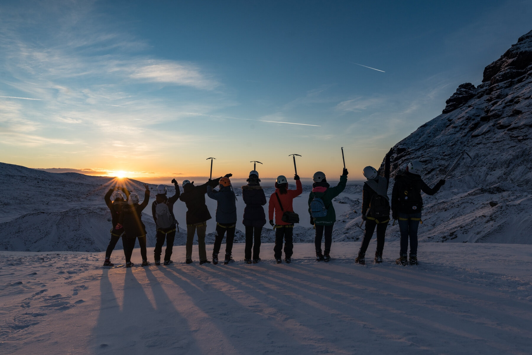 A group of people on a glacier at golden hour in Iceland