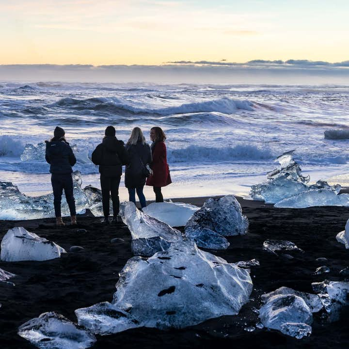 A group of people standing at the Diamond Beach in Iceland at Golden Hour