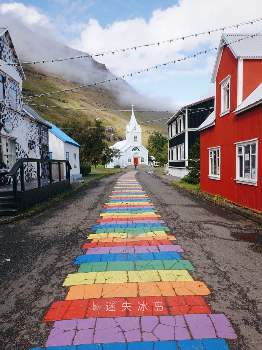 The town of Seyðisfjörður has an iconic blue church with a rainbow road leading up to it