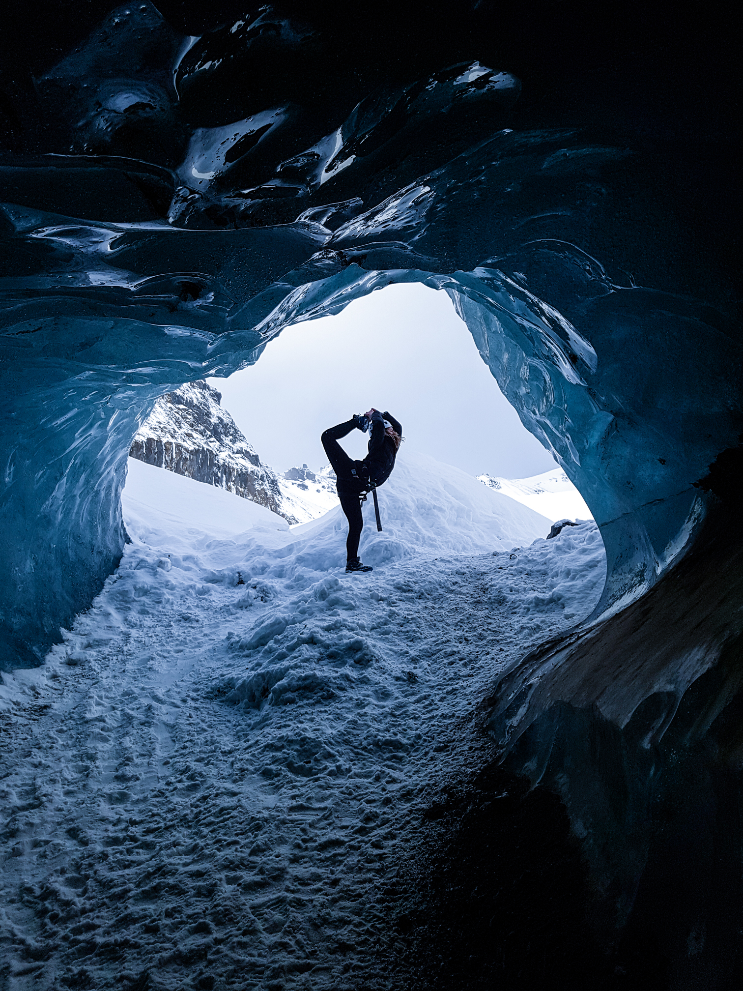 A woman doing a yoga pose within an ice cave in Iceland