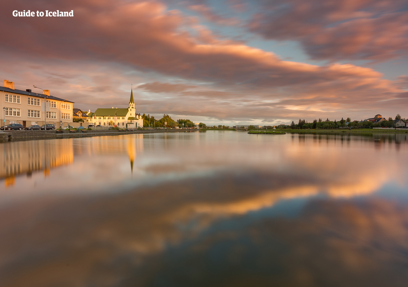 The city reflected in the waters of Tjörnin Pond in downtown Reykjavik.