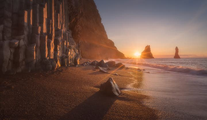 The sun setting in the background of the Reynisfjara Black Sand Beach on the South Coast of Iceland.